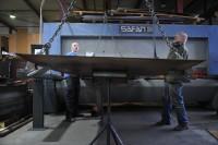06. Handig zo'n snijmachine. Leermeester Wim Sluiters en stagiair Dennie snijden de stroken voro de zijwanden.